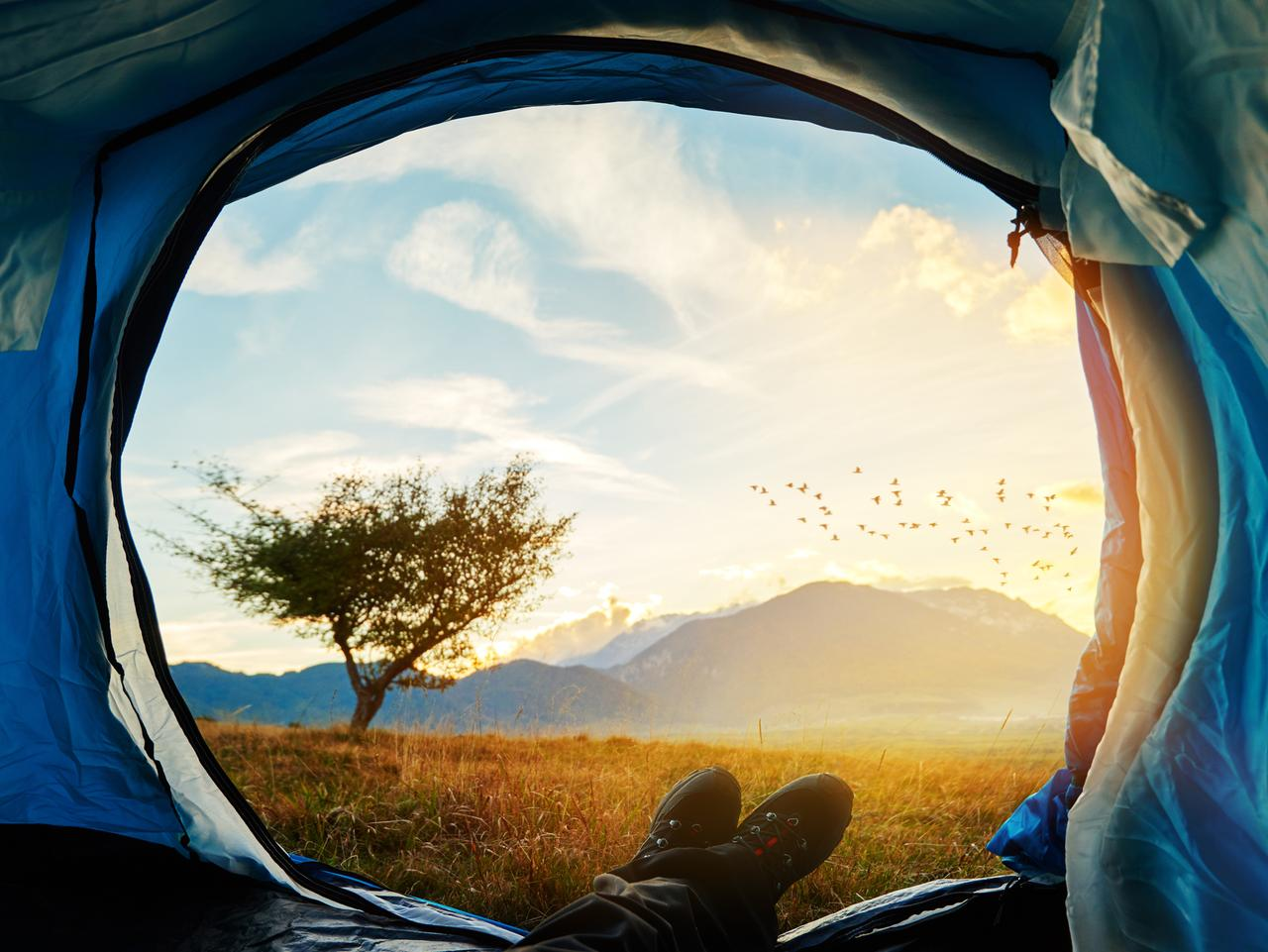 unrecognizable man legs resting in his tent, looking at sunset view of wild nature.adventure, exploration and freedom.