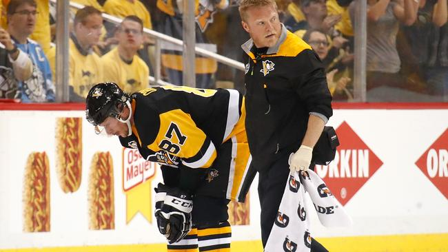 Sidney Crosby #87 of the Pittsburgh Penguins leaves the ice with trainer Chris Stewart after taking a hit in the first period.