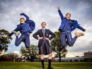 Kingswood College has switched a permanent sports day uniform. Dudman sisters Charlotte, (11) and Issey (13) jump for joy in their new outfits while Lucy Beck (13) wears the old uniform. Picture: Jake Nowakowski