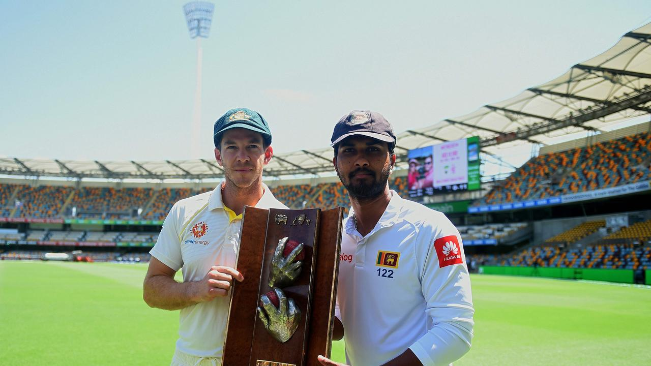 Dinesh Chandimal and Tim Paine pose with the Warne-Murali Test trophy at The Gabba.