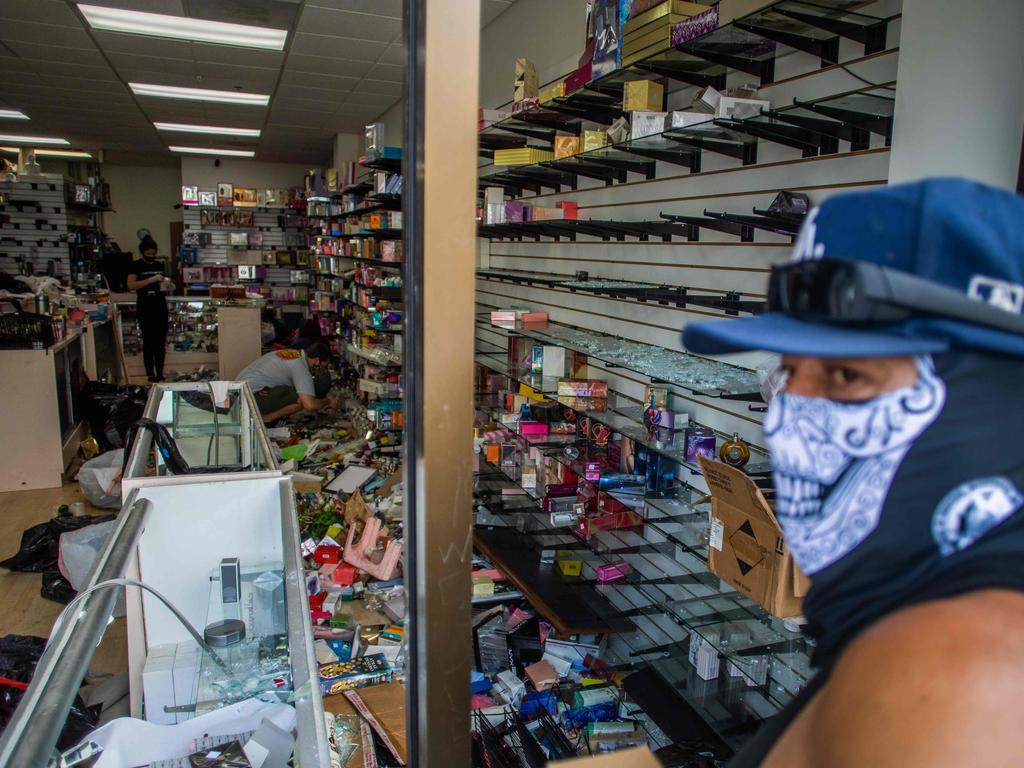 A man wearing a face cover looks at a looted store in downtown Long Beach. Picture: Apu Gomes/AFP