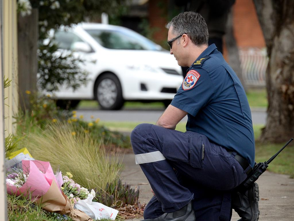 Lee, a paramedic, lays a floral tribute on behalf of the team at Ambulance Victoria's Westmeadows station. Picture: Andrew Henshaw