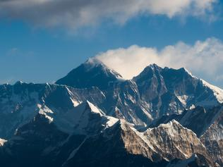 (FILES) This file photo taken on February 7, 2020 from a commercial aircraft shows an aerial view of Mount Everest (C) and the Himalayan mountain range, some 140kms (87 miles) north-east of Kathmandu. - The highest point on Earth got a bit higher on December 8 as China and Nepal finally agreed on a precise elevation for Mount Everest after decades of debate. The agreed height unveiled at a joint news conference in Kathmandu of 8,848.86 metres (29,031 feet) was 86 centimetres (2.8 feet) higher than the measurement previously recognised by Nepal, and more than four metres above China's official figure. (Photo by Jewel SAMAD / AFP)