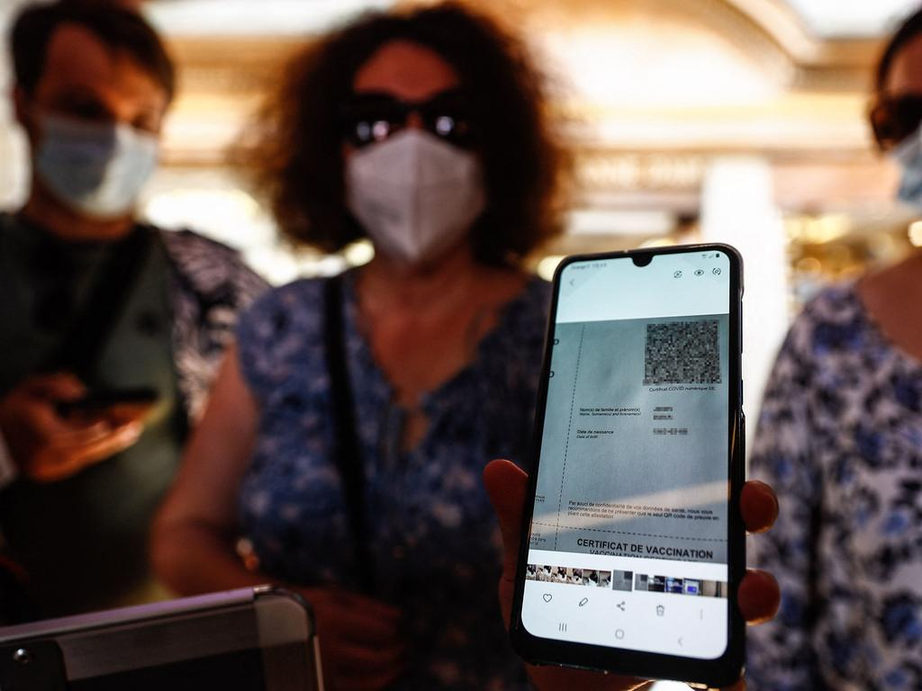 A woman shows her health pass as she arrives at a restaurant in Mont-Saint-Michel, in Normandy, northwestern France, on July 22, 2021. Picture: Sameer Al-Doumy/AFP