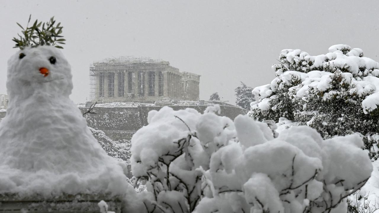 A snowman in front of the Parthenon temple atop the Acropolis in Athens. Picture: Aristotle Messinis/AFP