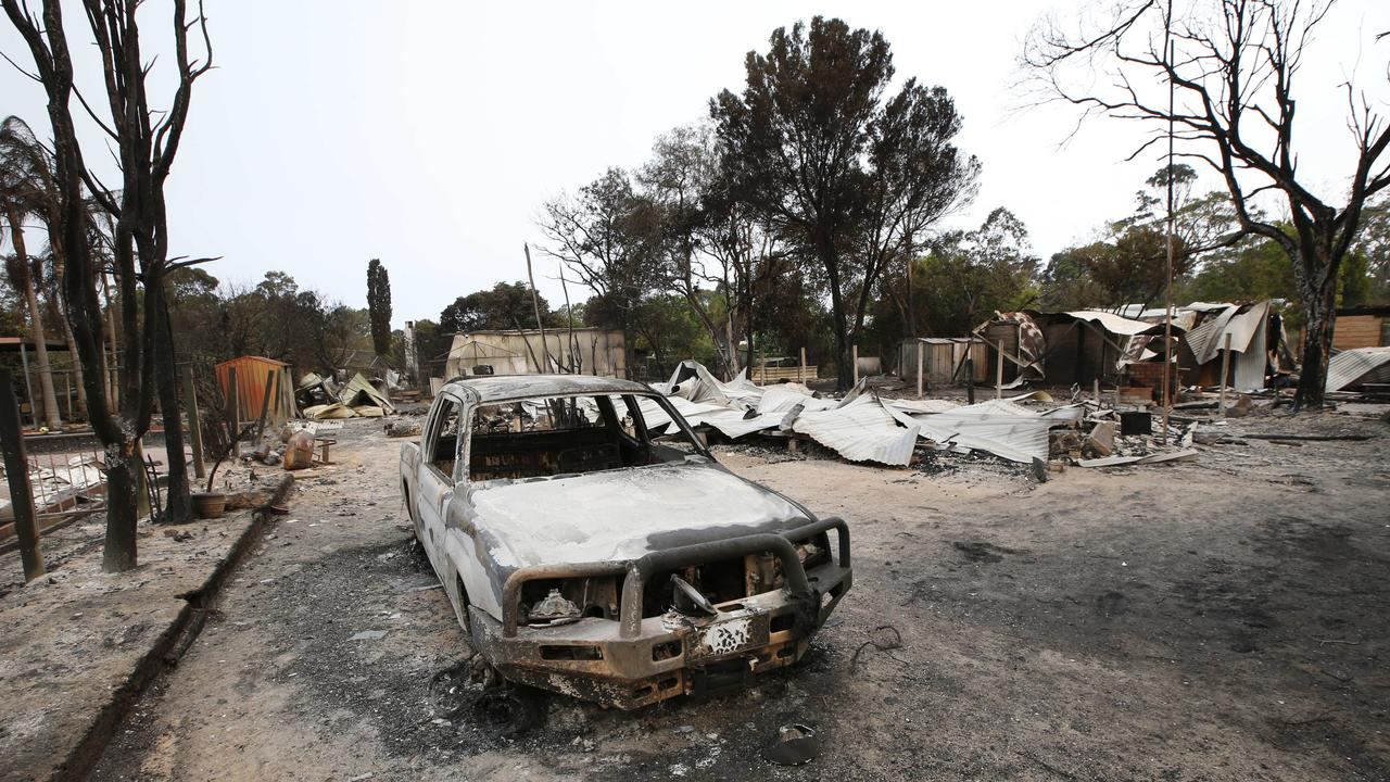 A burnt-out car and home in Mallacoota. Picture: David Caird