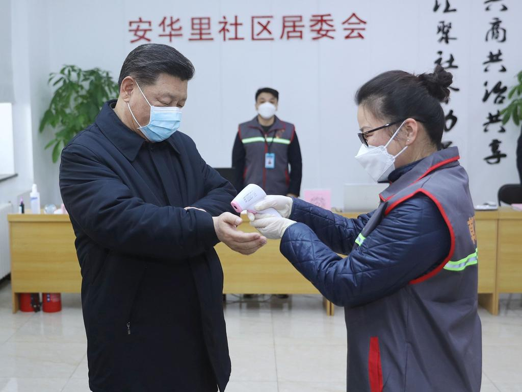 In a photo released by China's Xinhua News Agency, Chinese President Xi Jinping (L) is seen wearing a protective face mask as a health official (R) checks his body temperature. Picture: Ju Peng/Xinhua/AFP.