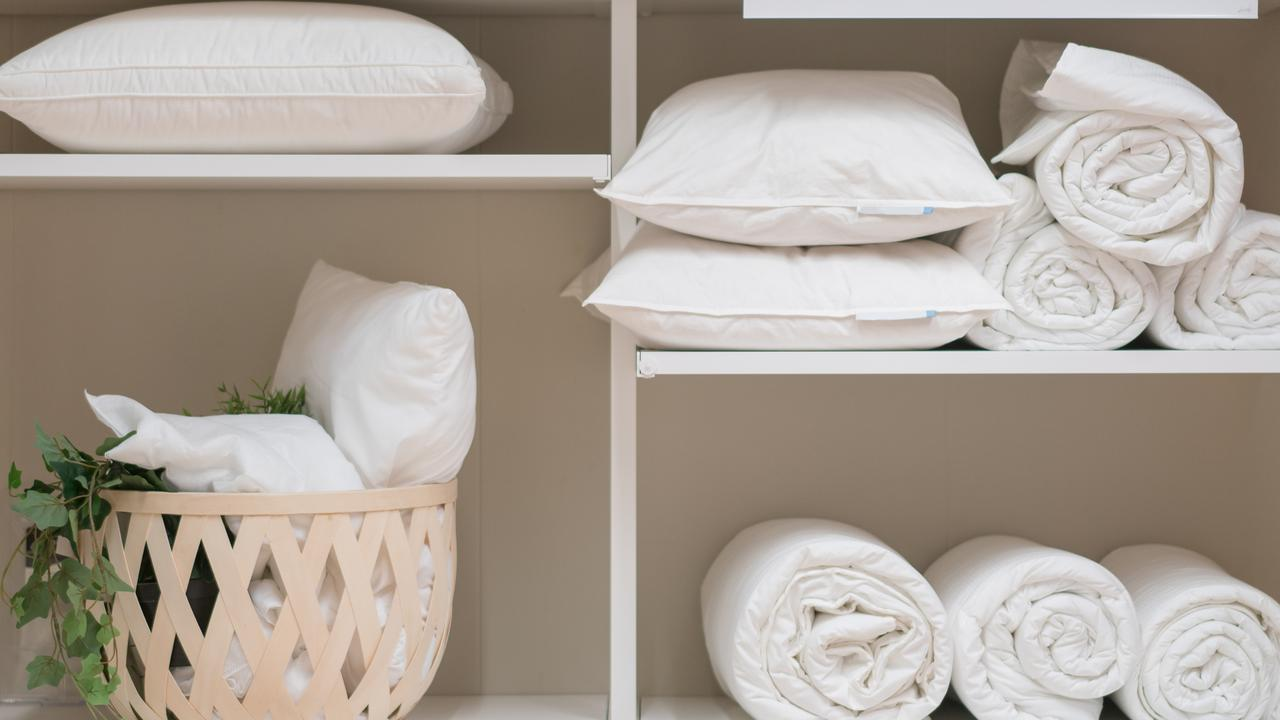 Various household items such as pillows and quilts standing in the white cupboard in the laundry room. Picture: iStock