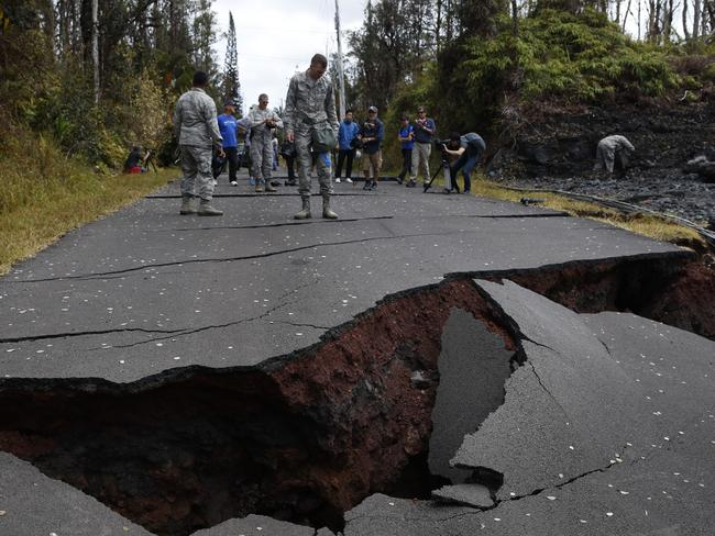 Volcanic activity has caused huge cracks, such as this one on the road near a residential housing estate. Picture: AP