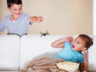 Mischievous young boy scaring his little sister on Halloween with a rubber spider