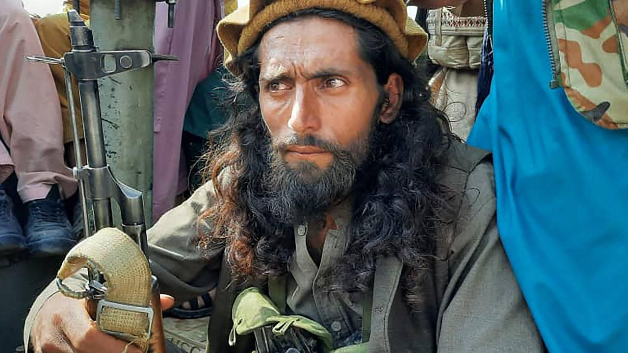 A Taliban fighter sits over a vehicle on a street in Laghman province on August 15, 2021. Picture: AFP
