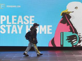 A woman walks past a sign urging people to stay home in Melbourne on August 14, 2020 as the city battles an outbreak of the COVID-19 coronavirus. - The state remains effectively sealed off from the rest of the country, with other regions so far largely spared from new infections. (Photo by William WEST / AFP)