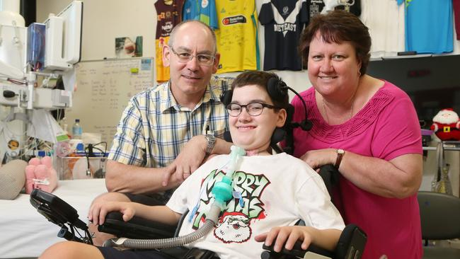 Samuel Thorne, with parents Craig and Jane, is hoping to return to the family home near Logan for Christmas Day, at least for a few hours. Picture: Jono Searle