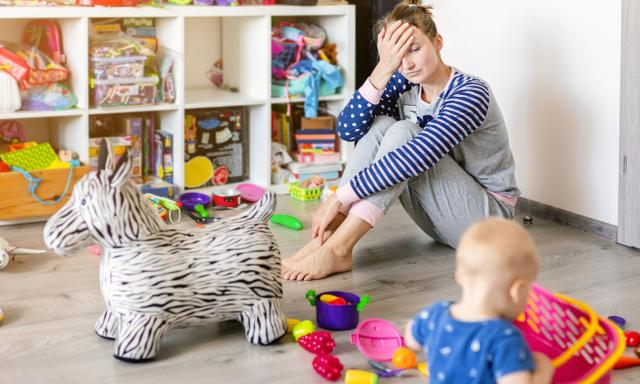 Tired of everyday household mother sitting on floor with hands on face. Kid playing in messy room. Scaterred toys and disorder. Happy parenting.