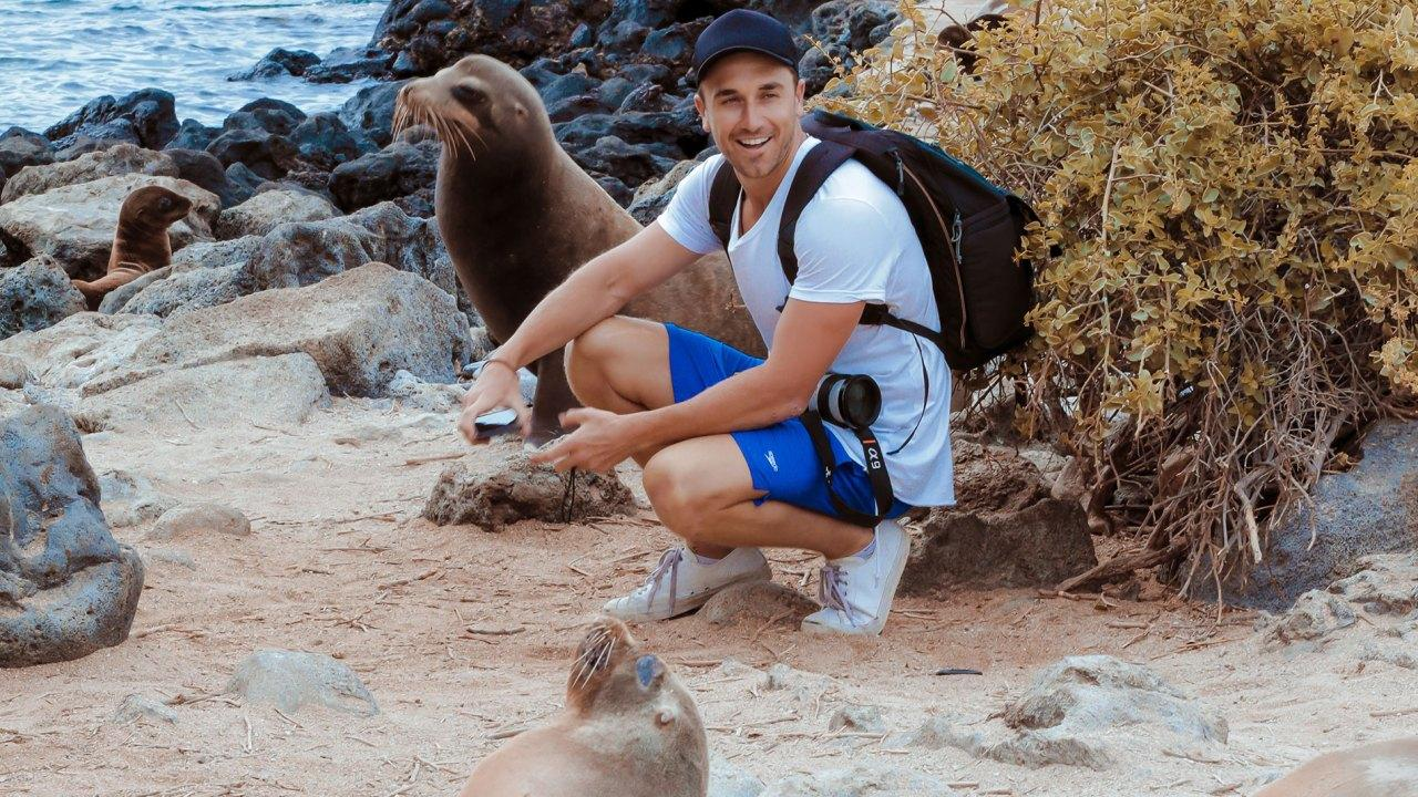 Tyson is surrounded by fur seals while exploring one of the many islands in the Galapagos. Picture: Robert K