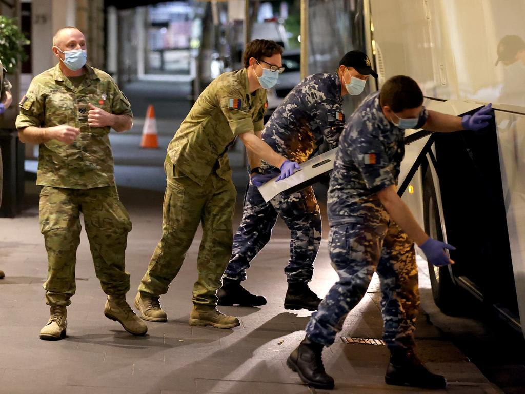 Members of the ADF help with the transfer of international arrivals into hotel quarantine at the Radisson Blu hotel in the Sydney CBD. Picture: Toby Zerna