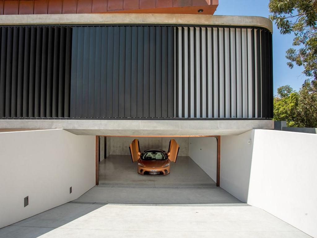 The garage is also clad in copper and note the vertical black blades angled for light and privacy.