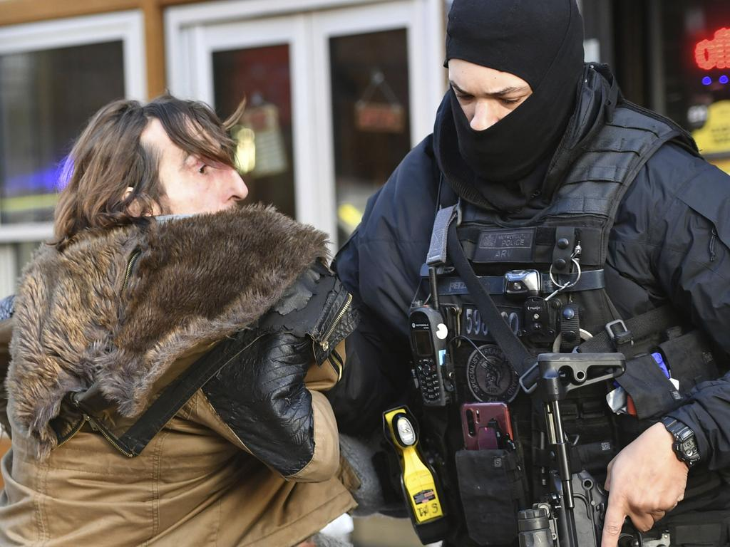 A police officer moves an uninvolved person away from a cordon. Picture: Dominic Lipinski/PA via AP.