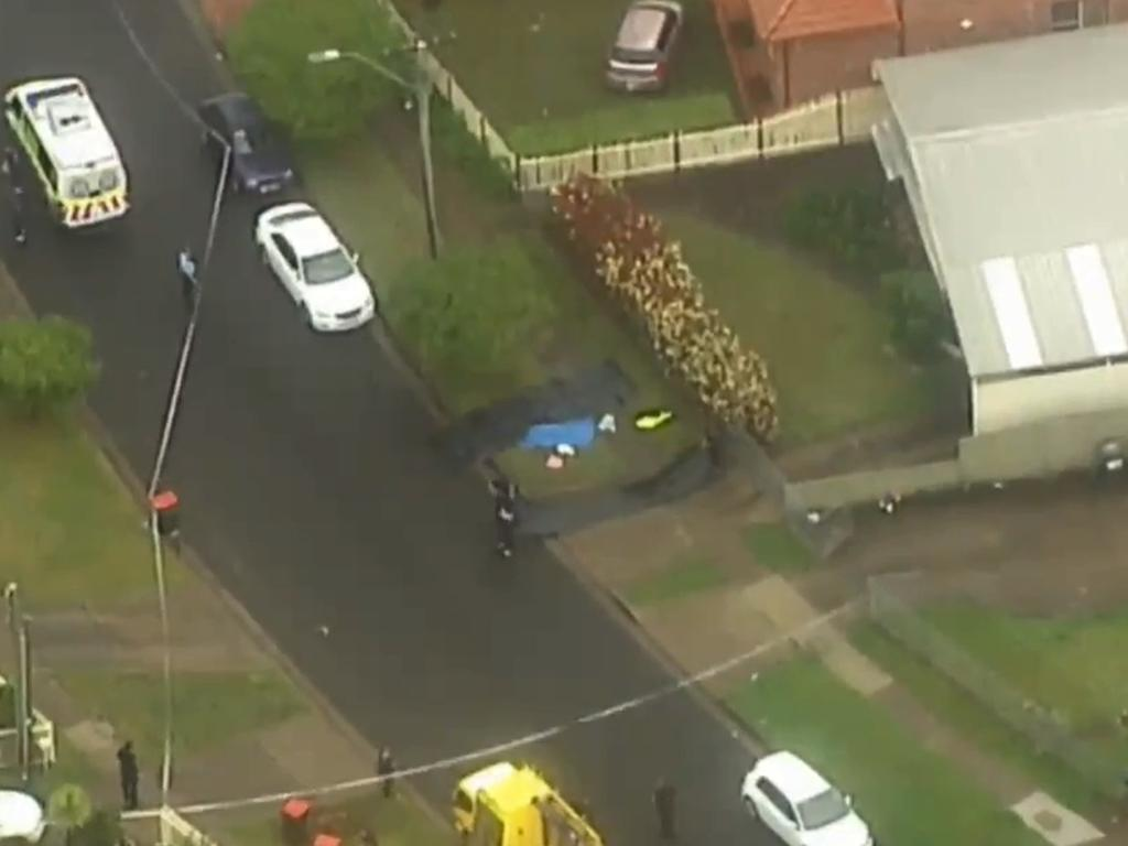 The victim's body lay under a blue tarp on a Blacktown property. Picture: 7 News