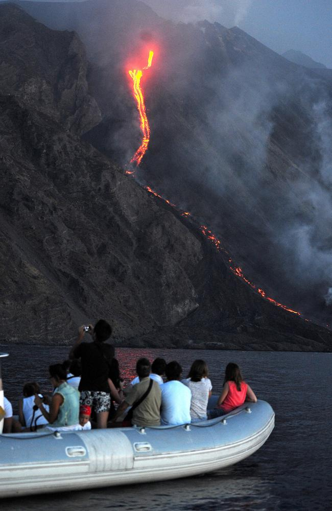 A boat of tourists watches as lava from the Stromboli volcano flows into the sea. Picture: Giovanni Isolino/AFP.