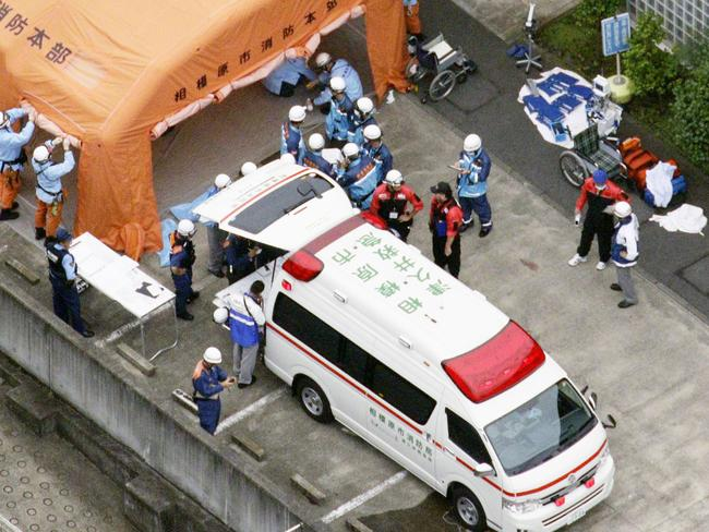 Ambulance crew and firefighters work outside a facility for the handicapped where a number of people were killed and dozens injured.