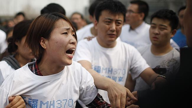 A relative of passengers on missing Malaysia Airlines flight MH370 yells at a security pe