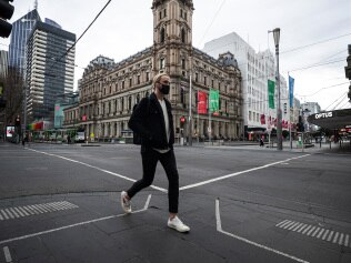 MELBOURNE, AUSTRALIA - JULY 20: A person crosses Bourke Street on July 20, 2021 in Melbourne, Australia. Victoria is under strict lockdown as the state continues to record new community COVID-19 cases and work to stop the spread of the highly infectious delta coronavirus strain in the community. (Photo by Daniel Pockett/Getty Images)