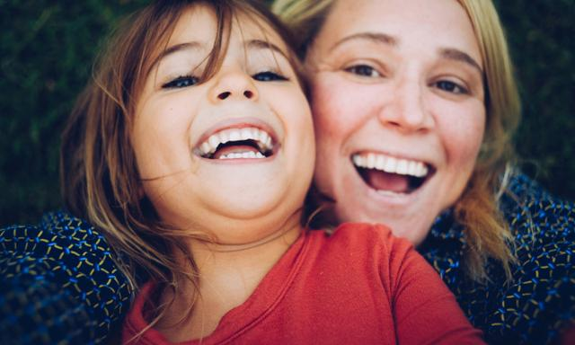 Mom, or woman in her thirties with 4 year old child, little girl, look solemn in a candid selfie style image