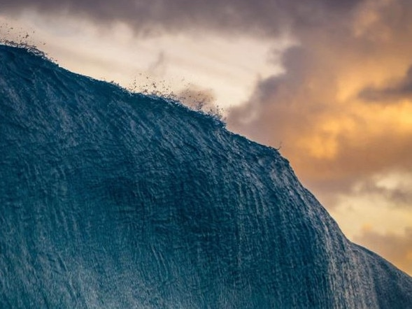 """SECOND PLACE, NATURE What happens before a wave breaks? On this particular day, the photographer decided to shoot the sunset on the east side of Oahu, Hawaii. He had to use a viewfinder while this wave was breaking. """"Not an easy task when a wave is about to crush you."""" Picture: Danny Sepkowski/National Geographic Travel Photo Contest"""