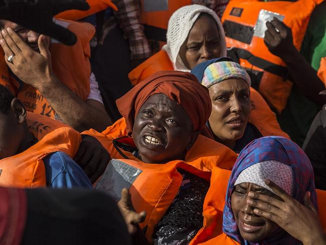 Migrants aboard a rubber dinghy off the Libyan coast receive aid from rescuers aboard the Open Arms aid boat, of Proactiva Open Arms Spanish NGO. Picture: AP