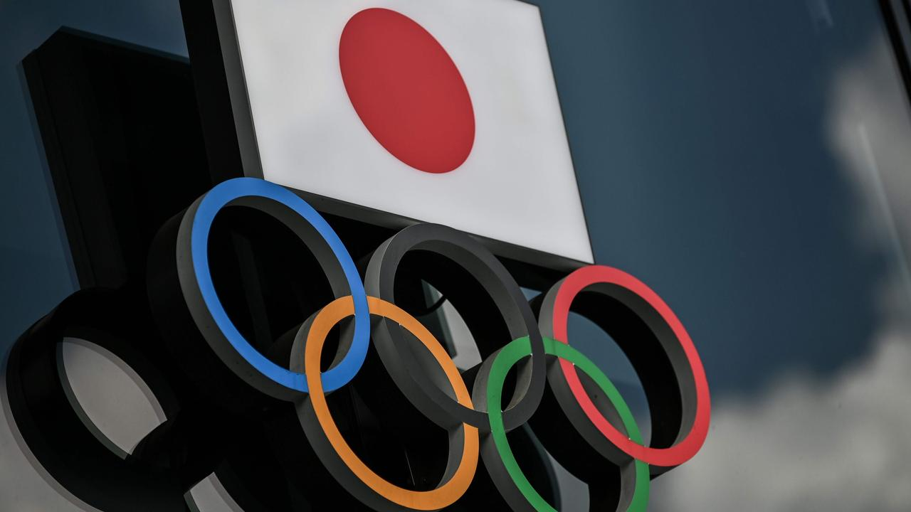 Olympic Rings and the Japanese flag are seen outside the Olympic Museum in Tokyo.