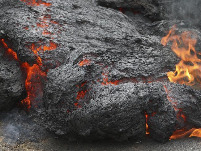 Lava burns across a road in the Leilani Estates subdivision near Pahoa, Hawaii. Picture: AP/Caleb Jones