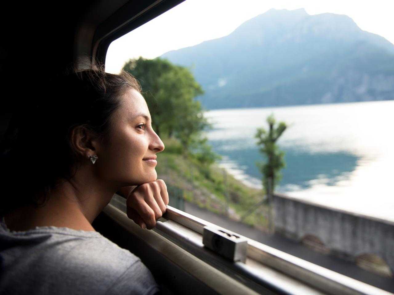 Smiling woman looking at the view from train