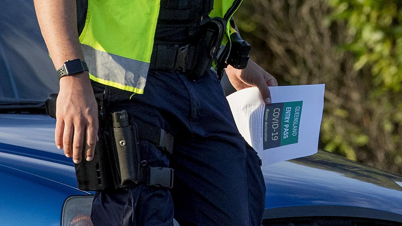Queensland police enforcing the QLD state border closer due to Coronavirus (COVID-19) and checking drivers as they cross from NSW to QLD at Gold Coast Highway at Bilinga. A police officer holding a Queensland Entry Pass for COVID-19 diaster declaration. Picture: Jerad Williams
