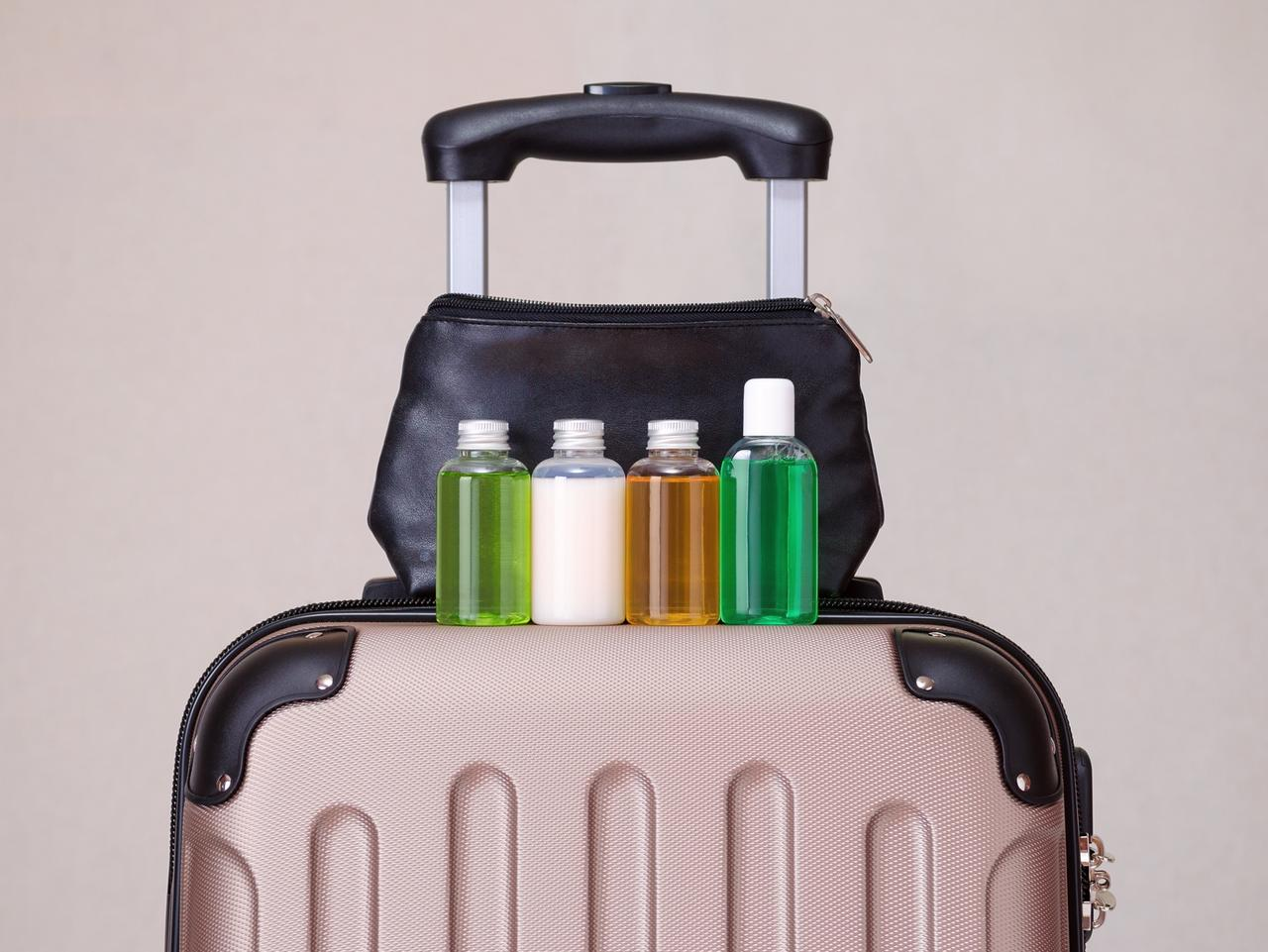 travel toiletries, small plastic bottles of hygiene products on the suitcase