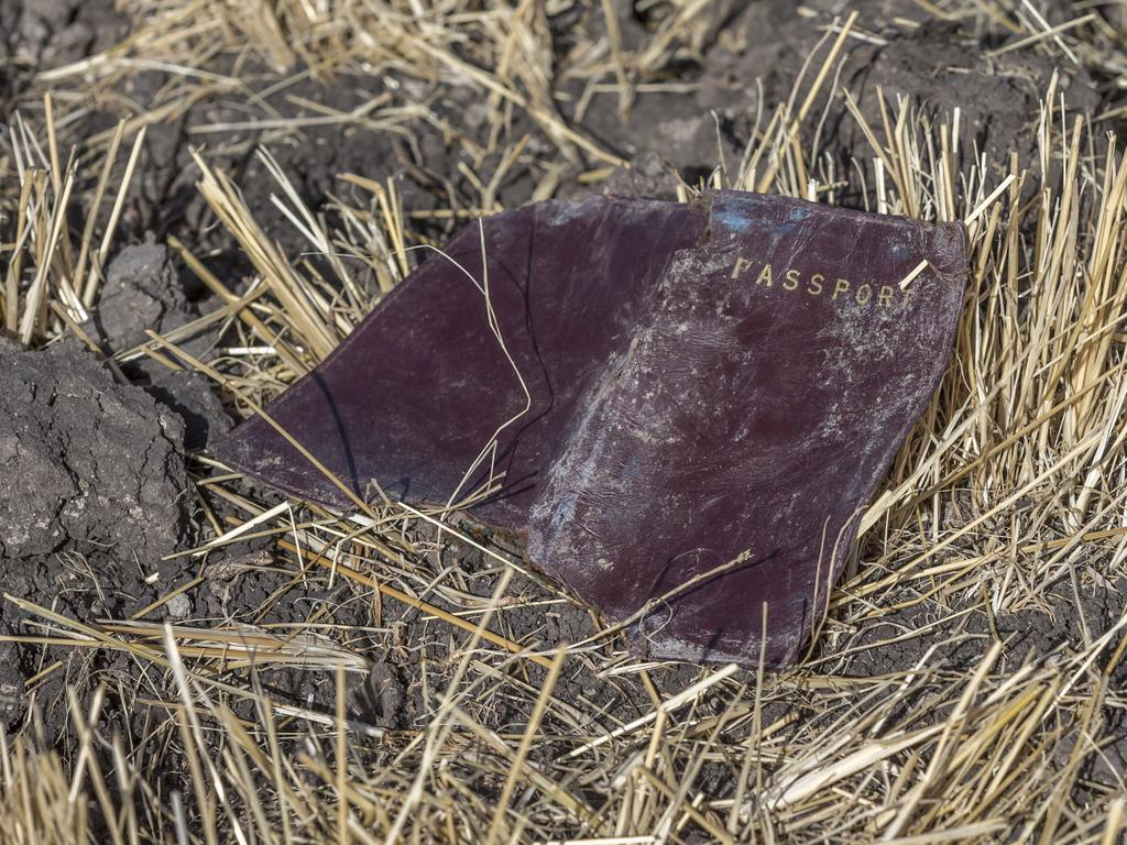A passenger passport lies on the ground at the scene of an Ethiopian Airlines flight crash. Share prices of Boeing Co. took a massive dive when markets opened on Monday. Picture: AP Photo/Mulugeta Ayene