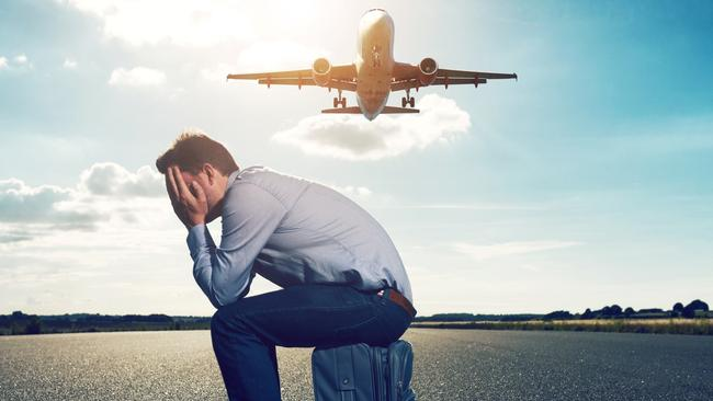 Sad passenger waits with suitcase for plane on runway