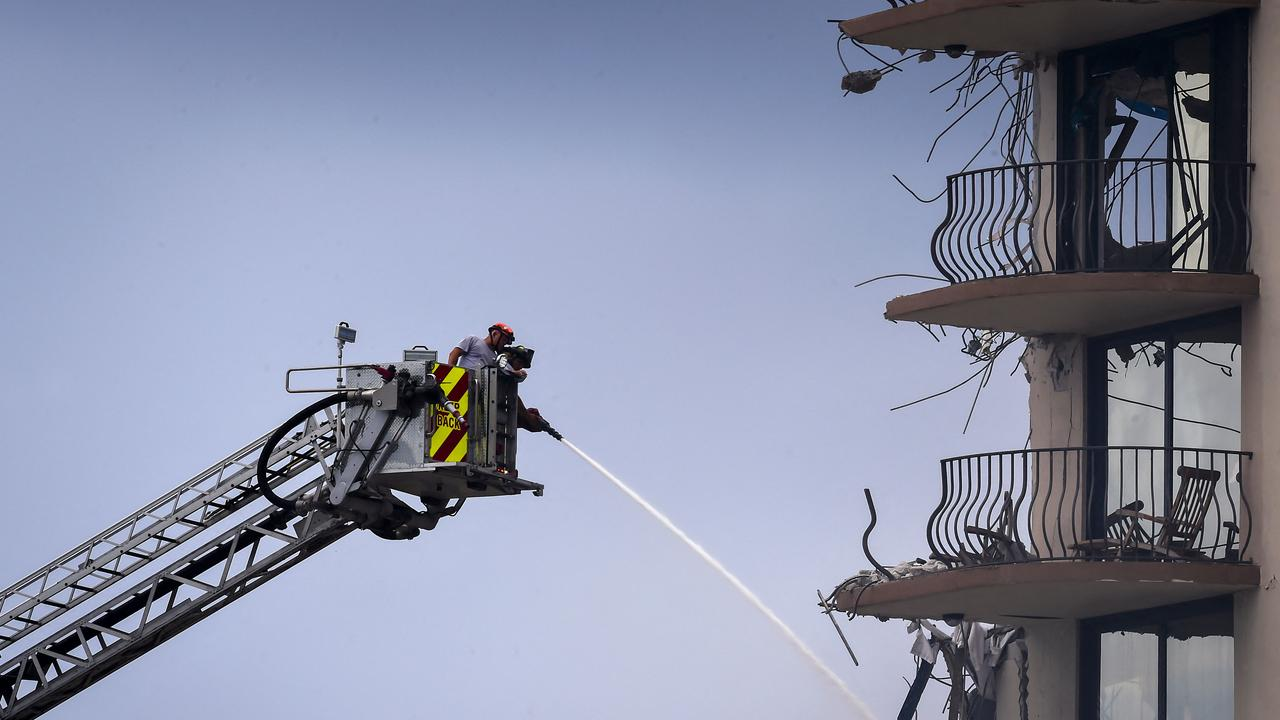 Fire Rescue firefighters spray water from a crane to the debris of the complex. Picture: Eva Marie UZCATEGUI / AFP