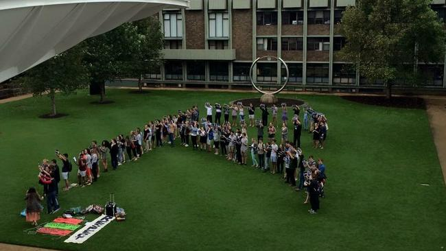 Students gather and form an 'R' for 'respect' at a demonstration on the lawns of UNSW after footage of college boys chanting sexist and vulgar songs was leaked.
