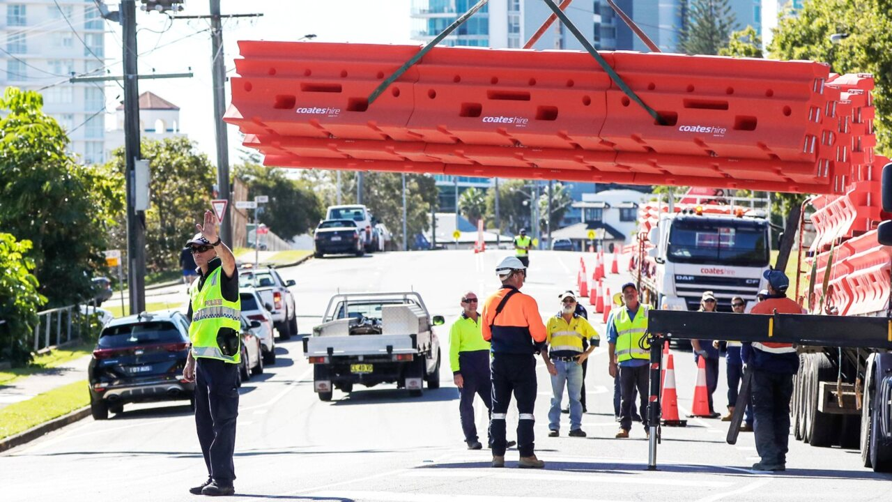 Peak delays and IT problems flare as Qld rolls back border restrictions