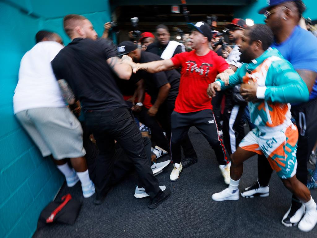 Floyd Mayweather and Jake Paul are separated by security. (Photo by Cliff Hawkins/Getty Images)