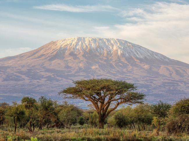 14. CLIMB MOUNT KILIMANJARO It's Tanzania's huge snow-capped mountain that looks like a painted backdrop over the Serengeti. And if you rate hiking up 5895m as an amazing travel experience then Mt Kilimanjaro is for you. The tough hike winds through four different landscapes but the smiles from those on the summit outrates all.