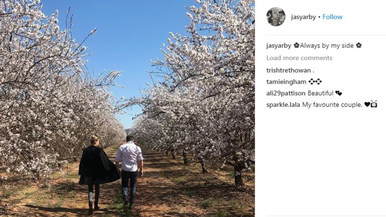 Instagram post by Jasmine of her and Karl in an almond orchard, saying 'always by my side'.