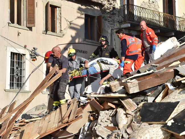 Rescuers clear debris while searching for victims in damaged buildings in Arquata del Tronto, Italy. Picture: Getty