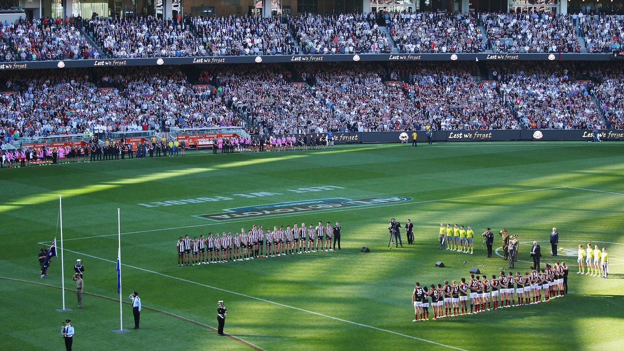 MELBOURNE, AUSTRALIA - APRIL 25: The players and crowd stand for a minutes silence in tribute to Anzac Day during the round five AFL match between the Collingwood Magpies and the Essendon Bombers at Melbourne Cricket Ground on April 25, 2016 in Melbourne, Australia. (Photo by Michael Dodge/Getty Images)