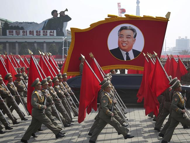 North Korean soldiers carry flags and a photo of late leader Kim Il Sung as they march across Kim Il Sung Square. Picture: AP