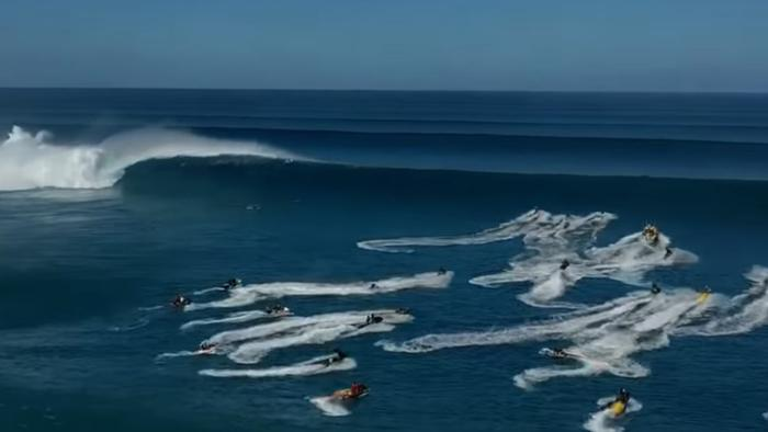 The jet skis desperately scramble to get over the wave.