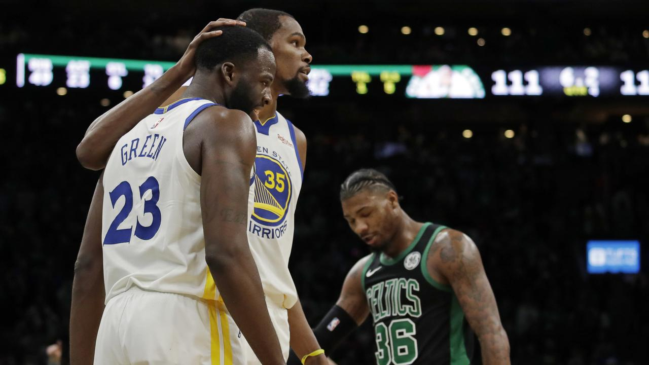 Golden State Warriors forward Kevin Durant (35) embraces teammate Draymond Green (23) as Boston Celtics guard Marcus Smart (36) walks by.