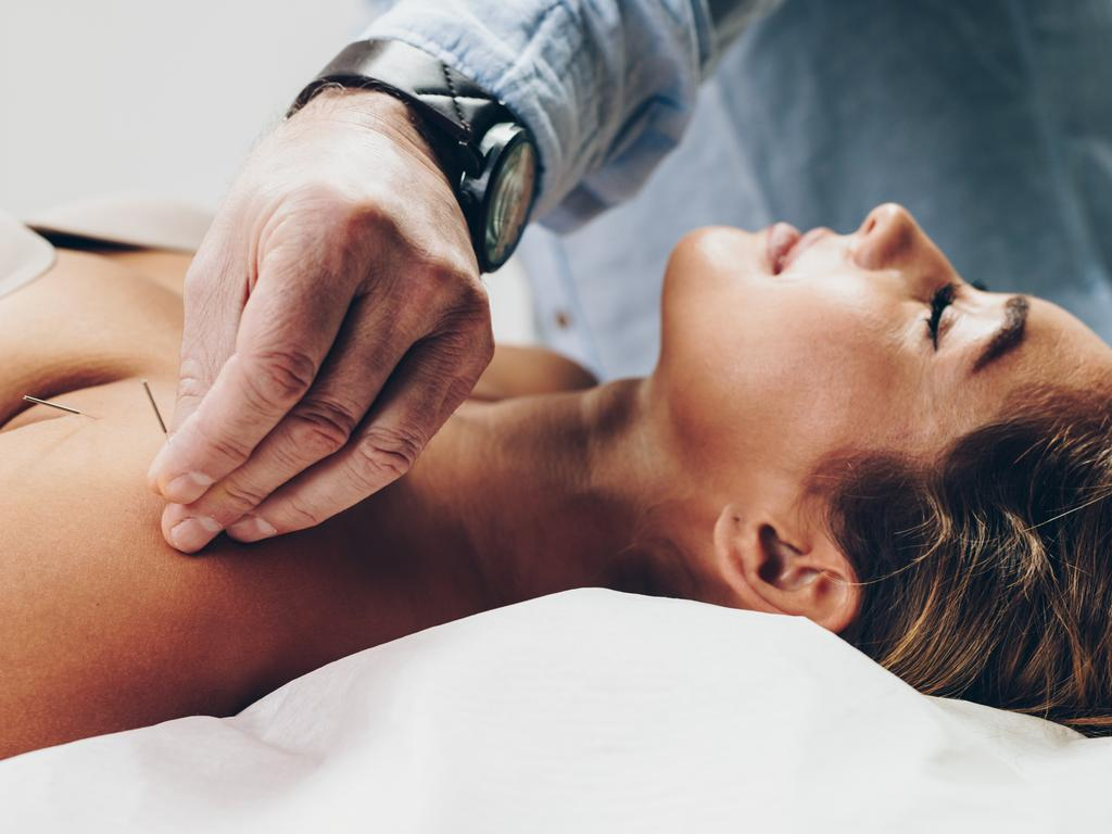 Beautiful young adult woman receiving professional acupuncture and massage treatment.