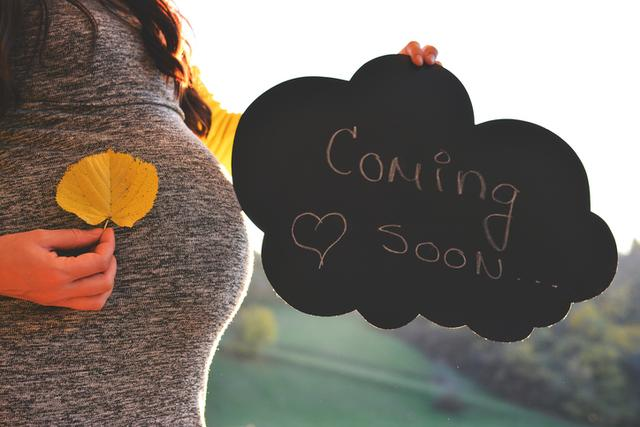 """Pregnant woman in the autumn park , holding a sign that says """"Coming soon""""."""